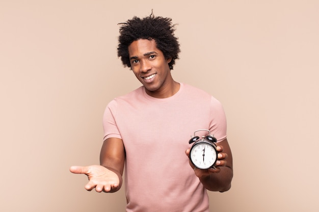 Jovem negro afro sorrindo feliz com um olhar amigável, confiante e positivo, oferecendo e mostrando um objeto ou conceito