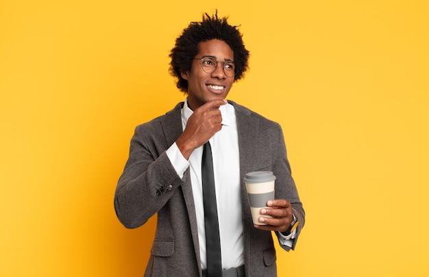 Jovem negro afro sorrindo feliz e sonhando acordado ou duvidando, olhando para o lado