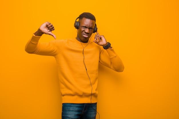 Jovem negro americano africano contra parede laranja com fones de ouvido