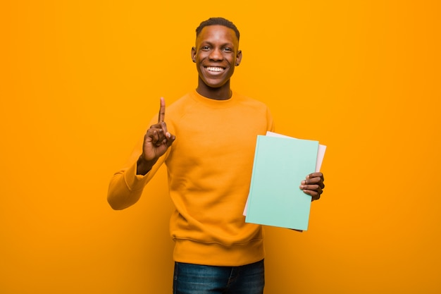 Jovem negro americano africano contra parede laranja com um livro