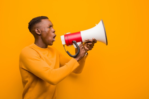 Jovem negro americano africano contra parede laranja com um megafone