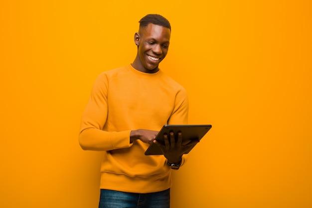 Jovem negro americano africano contra parede laranja com um tablet inteligente