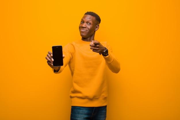 Jovem negro americano africano contra parede laranja com um telefone inteligente