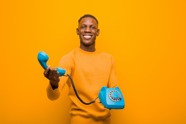 Jovem negro americano africano contra parede laranja com um telefone vintage