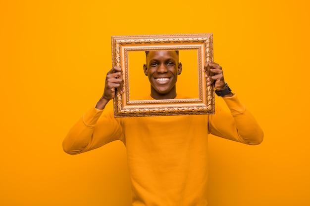 Jovem negro americano africano contra parede laranja com uma moldura barroca
