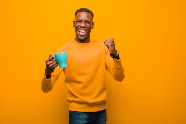Jovem negro americano africano contra parede laranja com uma xícara de café