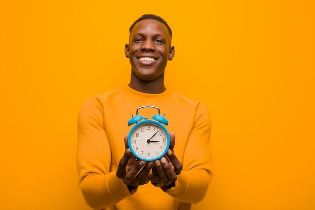 Jovem negro americano africano contra parede laranja segurando um despertador