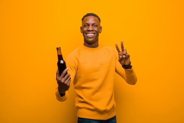 Jovem negro americano africano contra parede laranja tomando uma cerveja