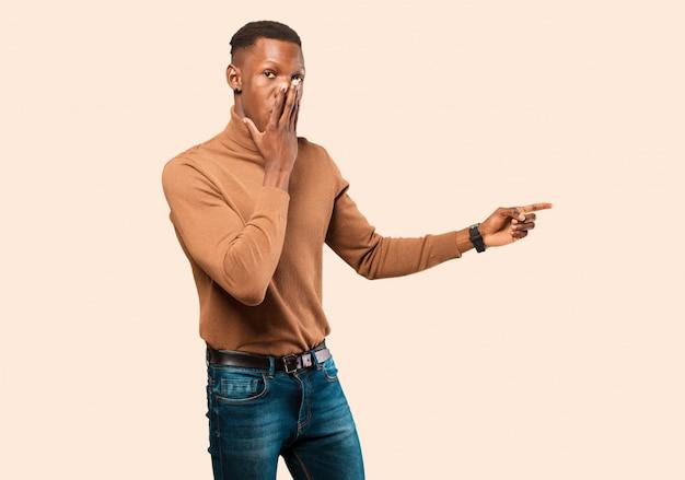 Jovem negro americano africano, sentindo-se feliz, chocado e surpreso, cobrindo a boca com a mão e apontando para o espaço da cópia lateral na parede bege