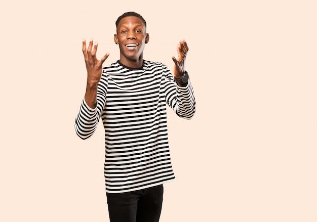 Jovem negro americano africano, sentindo-se feliz, espantado, sortudo e surpreso, comemorando a vitória com as duas mãos no ar contra a parede bege