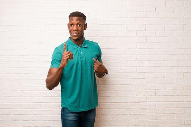 Jovem negro americano africano, sentindo-se orgulhoso e surpreso, apontando para si mesmo com confiança, sentindo-se como o número um bem-sucedido contra a parede de tijolos