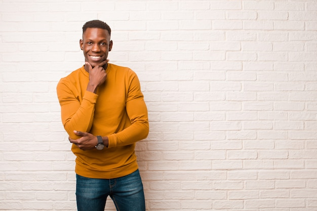 Jovem negro americano africano sorrindo com uma expressão feliz e confiante com a mão no queixo, pensando e olhando para o lado contra a parede de tijolos