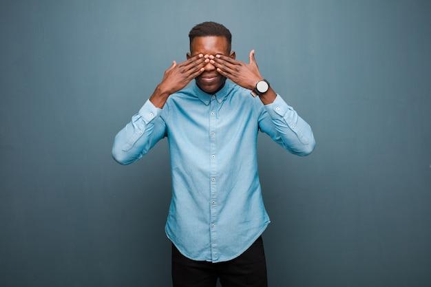 Jovem negro americano africano sorrindo e se sentindo feliz, cobrindo os olhos com as duas mãos e esperando a surpresa inacreditável