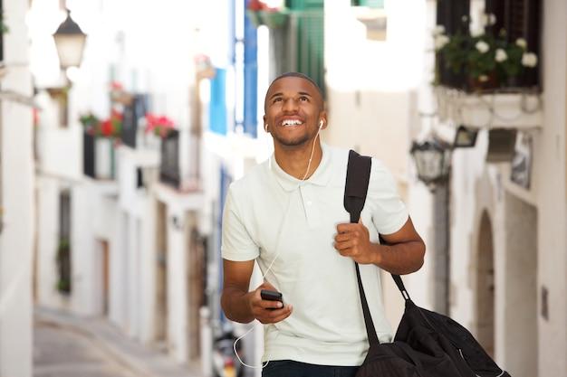 Jovem negro andando e ouvindo música com fones de ouvido e telefone inteligente
