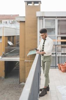 Jovem negro ao ar livre usando telefone inteligente