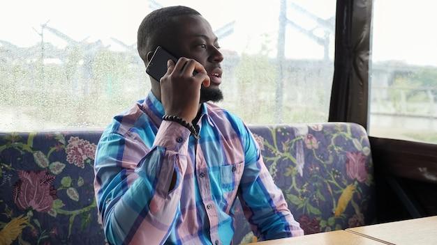 Jovem negro barbudo está falando no celular. homem afro-americano está ligando para smartphone sentado no café esperando seu pedido. cara no café da barraca de verão, sentado no sofá.