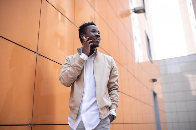 Jovem negro bonito em uma jaqueta e camisa branca está ouvindo música com fones de ouvido
