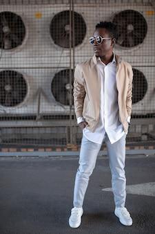 Jovem negro bonito em uma jaqueta e camisa branca na rua
