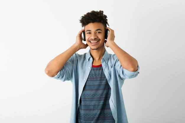 Jovem negro bonito, ouvindo música em fones de ouvido, expressão facial sorridente, humor positivo, emoção feliz, isolado no fundo branco, juventude afro-americana, estilo hippie, estudante