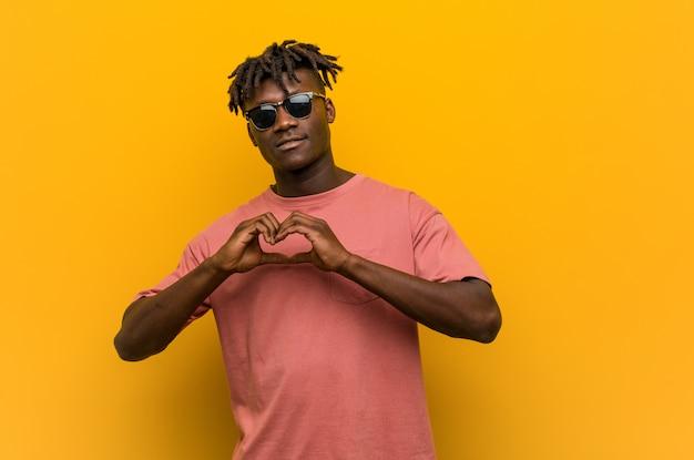 Jovem negro casual usando óculos de sol sorrindo e mostrando uma forma de coração com as mãos.