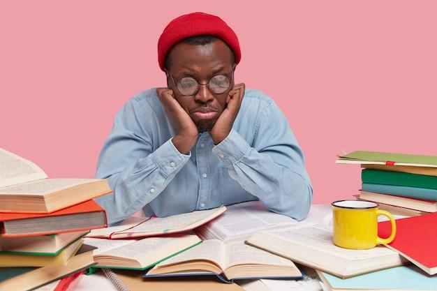Jovem negro chateado com o olhar voltado para baixo, sente-se deprimido e triste enquanto lê livros há muito tempo, usa óculos redondos, chapéu vermelho e camisa
