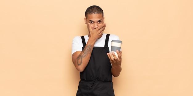 Jovem negro cobrindo a boca com as mãos com uma expressão chocada e surpresa, mantendo um segredo ou dizendo oops