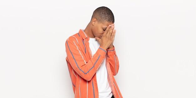 Jovem negro cobrindo os olhos com as mãos com uma expressão triste e frustrada de desespero, chorando, vista lateral