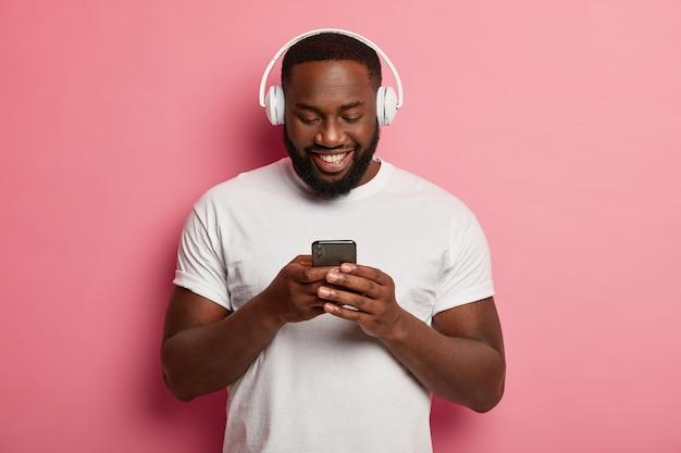 Jovem negro com a barba por fazer ouve uma transmissão de rádio online, usa fone de ouvido, segura um celular moderno, passa o tempo livre ouvindo música
