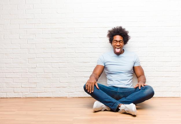 Jovem negro com atitude alegre, despreocupada, rebelde, brincando e enfiando a língua para fora, se divertindo sentado no chão em casa