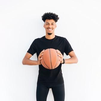 Jovem negro com basquete, olhando para a câmera