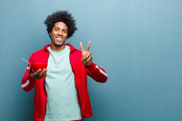 Jovem negro com uma tigela de café da manhã contra a parede azul grunge