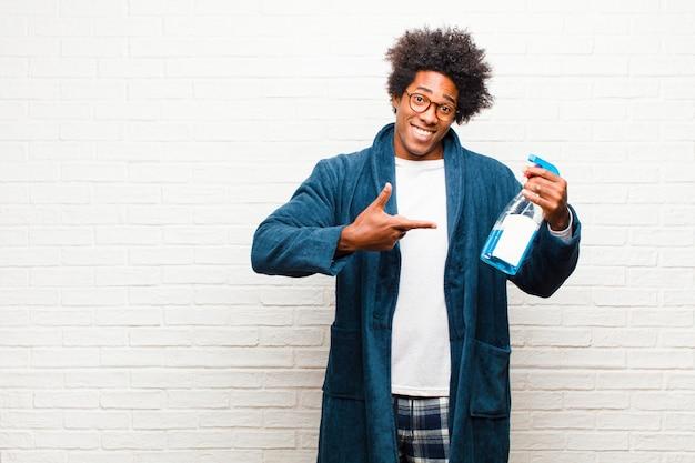 Jovem negro de limpeza com produto limpo