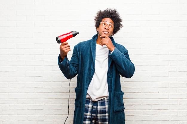 Jovem negro de pijama com um secador de cabelo contra a parede de tijolos