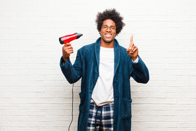 Jovem negro de pijama com um secador de cabelo contra tijolos