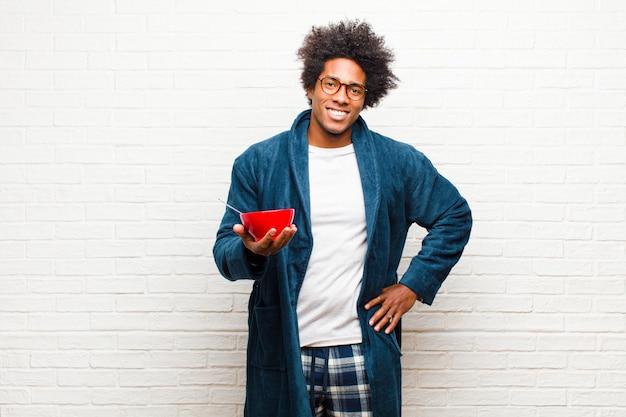 Jovem negro de pijama com uma tigela de café da manhã