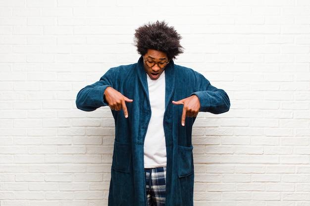 Jovem negro de pijama com vestido com a boca aberta, apontando para baixo com as duas mãos, olhando chocado, surpreso e surpreso