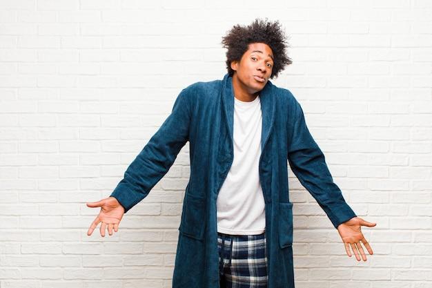 Jovem negro de pijama com vestido sem noção e confuso, sem ter ideia, absolutamente intrigado com um olhar idiota ou tolo contra a parede de tijolos