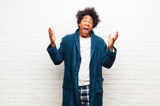 Jovem negro de pijama com vestido, sentindo-se feliz, animado, surpreso ou chocado, sorrindo e surpreso com algo inacreditável contra a parede de tijolos