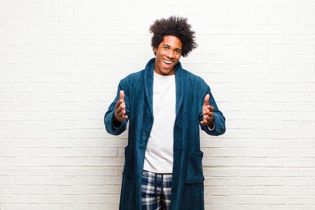 Jovem negro de pijama com vestido sentindo-se feliz, atônito, sortudo e surpreso, como dizer omg a sério? inacreditável