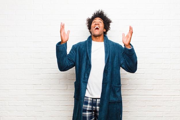 Jovem negro de pijama com vestido, sentindo-se feliz, espantado, sortudo e surpreso, comemorando a vitória com as duas mãos no ar