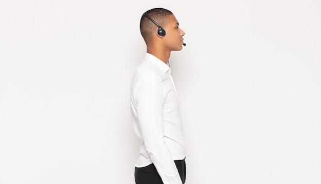 Jovem negro em vista de perfil olhando para copiar o espaço à frente, pensando, imaginando ou sonhando acordado