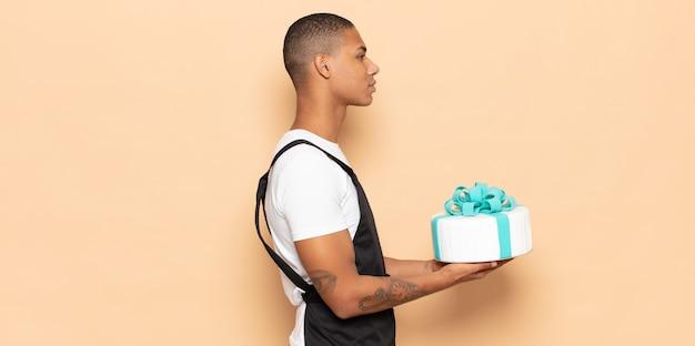 Jovem negro em vista de perfil olhando para copiar o espaço à frente