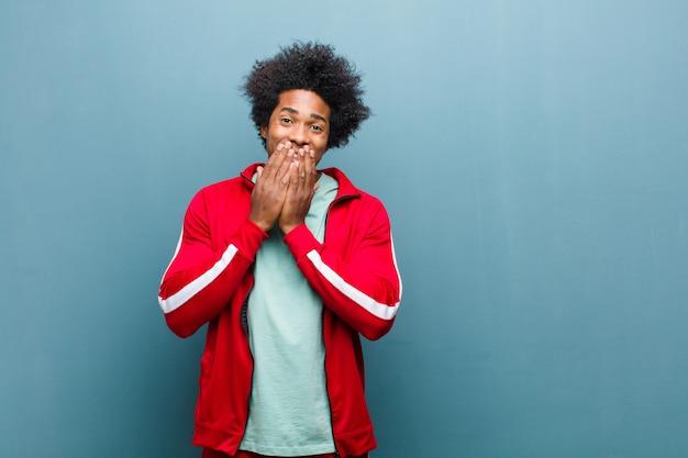 Jovem negro esportes feliz e animado, surpreso e espantado cobrindo a boca com as mãos, rindo com uma expressão fofa contra grunge