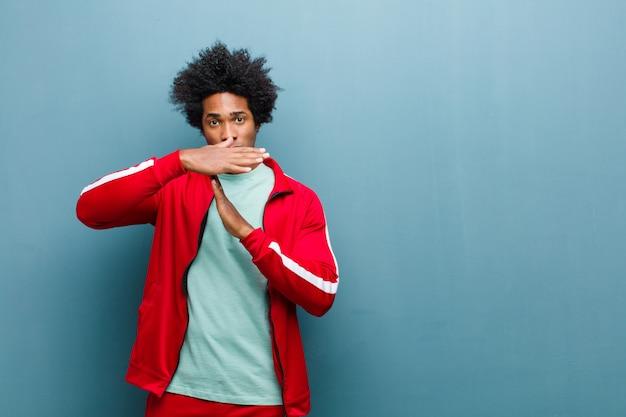 Jovem negro esportes olhando sério, popa, irritado e descontente, fazendo sinal de tempo contra a parede do grunge