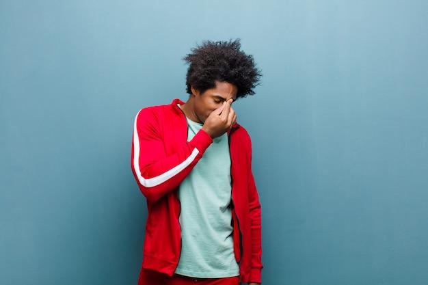 Jovem negro esportes sentindo estressado, infeliz e frustrado, tocando a testa e sofrendo de enxaqueca de forte dor de cabeça contra a parede do grunge