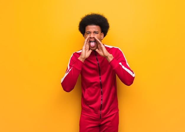 Jovem negro esportivo sentado em uma parede laranja gritando algo feliz na frente