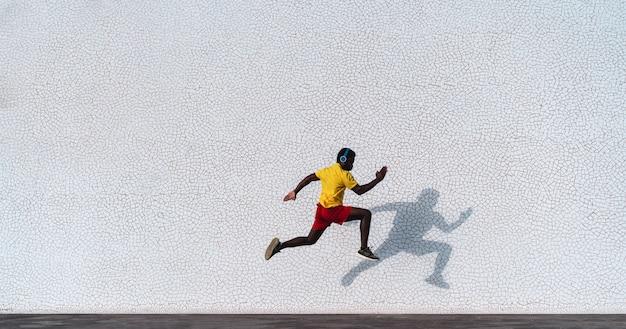 Jovem negro, fazendo a rotina de exercícios durante a manhã, enquanto corre ao ar livre