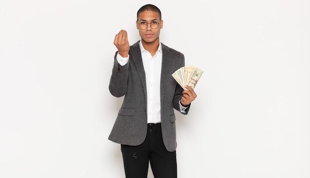 Jovem negro fazendo capice ou gesto de dinheiro, mandando você pagar suas dívidas!