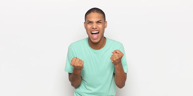 Jovem negro gritando agressivamente com olhar irritado, frustrado e raivoso e punhos cerrados, sentindo-se furioso
