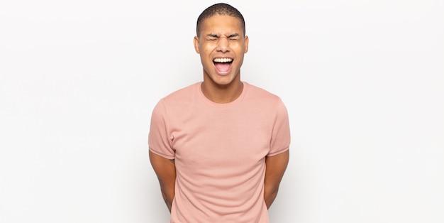 Jovem negro gritando agressivamente, parecendo muito zangado, frustrado, indignado ou irritado, gritando não